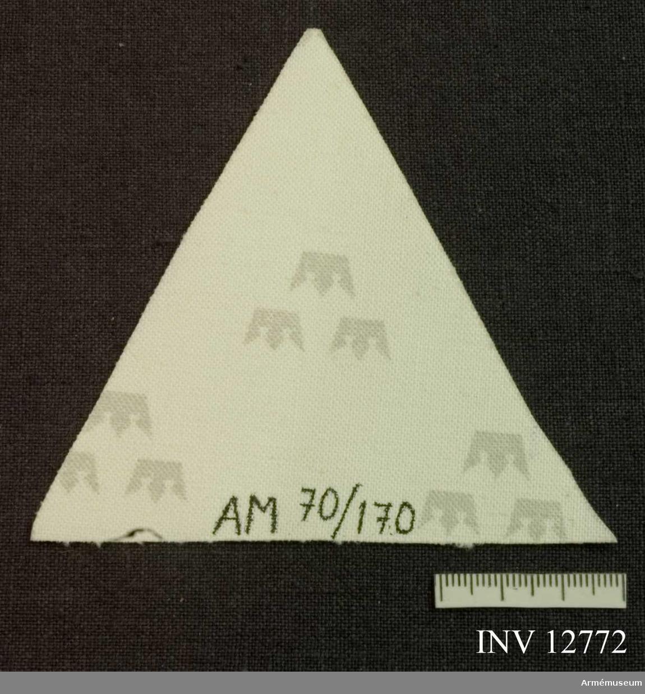 Samhörande nr är 12771. Grupp C I. Av lysväv (reflexer).Märket bäres vid 7. kompaniet, Kungliga Svea livgarde, och fäst på höger byxben över vaden på fältbyxa m/1958 och m/1959. Litet märke bäres av befäl, och stort av åldersklassen. (Tecknet är kompaniets traditionella och symboliserar en stjärnas  trigonalsken, enl. I 1 Rey I.) Märket har på detta sätt burits sedan mitter av 1960-talet.