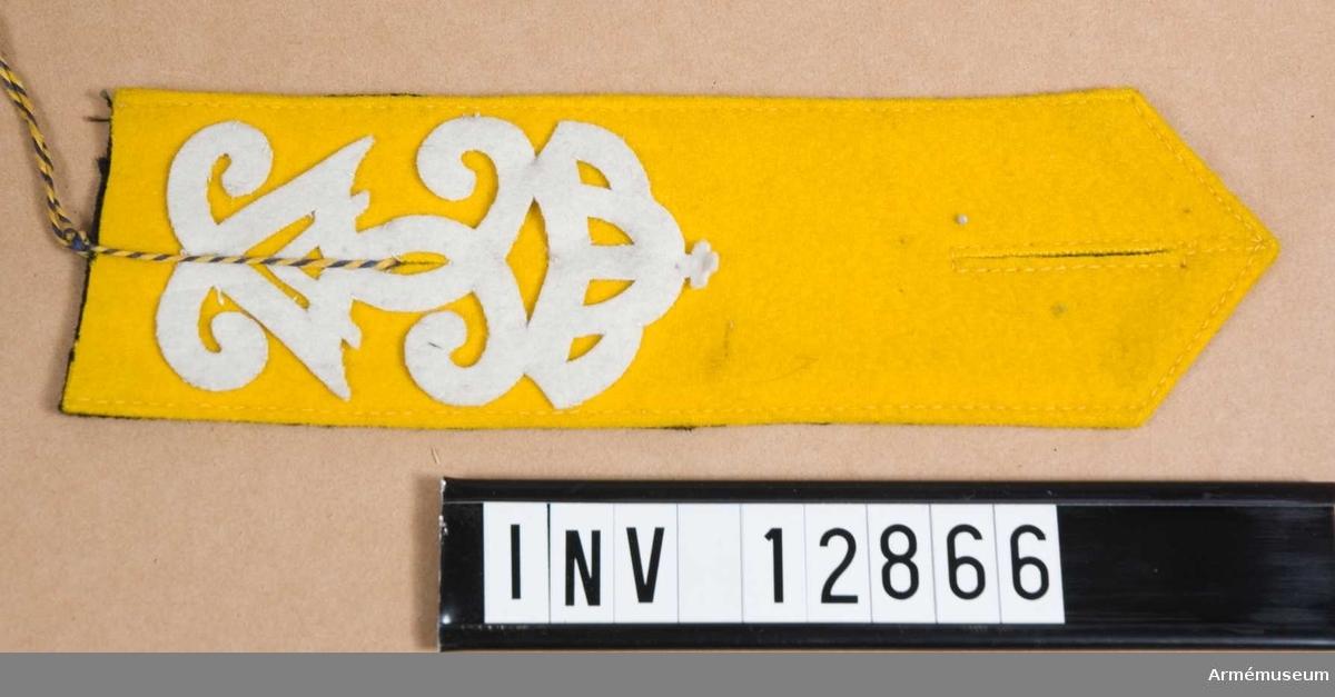 Grupp C I. Modell och namnchiffer av tyg att anbringas på axelklaffar till vapenrockar och kappor till uniform av äldre modell än m/1910 vid I 1, I 2 och K 1, i den mån metallnamnchiffer m/1908 icke kunnat anskaffas. Deposition från Arméförvaltningens intendenturdep., modellkammaren.