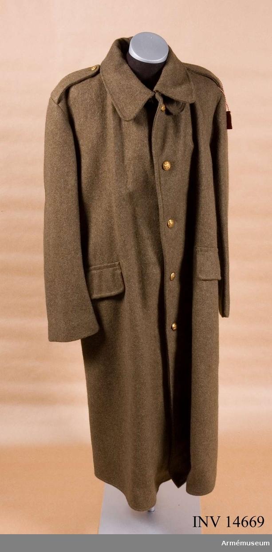 """Grupp C I. Kappa m knapp, menig, England. Deponerad från  K.A.I.D. Tillverkad i England. ÖVERROCK av khakifärgat kläde, enradigt (fem knappar). Baktill i livet en sleif, som består av två delar; en med tre knapphål och den andra med tre knappar, en slits 500 mm lång med två knapphål och knappar. AXELKLAFFAR av samma kläde, 70 mm breda och 120 mm långa, fastsydda vid ärmsömmarna, samt knäppta vid överrocken med knappar av mindre format. FICKOR två sido- raka, 240 mm långa med lock, som stänges med små benknappar på inre sidan. FODER av ylletyg på överrockens övre del. På fickan stämpel: """"145 W"""" uppåtriktad pil """"D"""", under pilen """"M"""". På klädet är klistrad en papperslapp med skriften """"Milus? Cartwright, Reynolds & Co Ltd"""" (firmans etikett) """"1917"""" """"Size No 6"""" - storlek, """"Height 5/7 x 8"""" - höjd, """"Breast 37 - 39"""" - bröst. KNAPPAR alla av metall, guldfärgade, 25 mm i diameter, fem st på framsidan. På axelklaffarna, sleif och slits  - sju st, 17 mm i diameter. På alla knappar engelska statsvapnet. KRAGE liggande med hake och hyska. Under kragen finns tre benknappar och sleif för att stänga kragen. ÄRMUPPSLAG 100 mm höga med avrundade vinklar. LITTERATUR: Enligt Handbuch der Uniformskunde. Professor Richard Knötel. Hamburg. 1937 sidan 203. Efter år 1870 och boerkriget fick engelsmännen erfarenhet av att införa khakiuniformen i armén. Redan år 1901 blev khakiuniformen införd som officiell fältuniform i engelska armén. Arméen Album II. Die Englischen Armée und Marine uniformen im Kriege. Leipzig. Verlag v. M. Ruhl. Sidan 12. Der Mantel av khakifärgat kläde. Bilaga. Die Englische Armée. Infanterist i samma mantel med en knapprad i färgbild."""