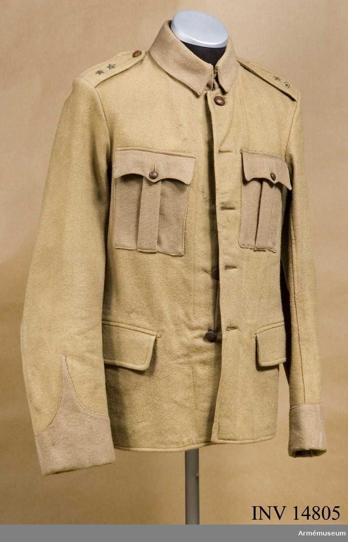 """rupp C I. Uniformen för löjtnant i engelsk tjänst under boerkriget, E. Mossberg, sedermera överste. Rocken användes under boerkriget av överste E. Mossberg, som då hade kaptens rang.  Gåva från överste E. Mossbergs sterbhus. Vapenrock av beigefärgat khakityg, enradig m fem knappar, 610 mm lång. På sidorna sprund, 90 mm långa. Axelklaffar av samma tyg, 55 mm breda och 130 mm långa, fastsydda vid ärmsömmarna samt fästade vid vapenrockens med små knappar. Axelklaffarna har två stjärnor - kaptens grad. Fyra fickor: två sidofickor och två bröstfickor (bröstfickorna är försedda med vertikala veck och gjorda av annat ylletyg). Alla fickorna har lock och bröstfickorna även små knappar. Foder saknas. På klädets insida en påklistrad papperslapp med påskrift """"Sege Drab"""" """"Size No 27"""" """"Height 5 ft 11 & 6"""" """"Breast 40"""" """"Waist 35"""" """"Knight & Son"""" (firmanamn) """"1900"""". På vapenrockens insida finns en ficka. Knapparna är alla av läder, brunfärgade, 20 mm i diameter - två på axelklaffarna och två på bröstfickorna. Ståndfällkrage, av annat kläde än rocken (samma som bröstfickorna och ärmuppslagen) med två hyskor och hakar. Ärmuppslagen i vinkelform av annat kläde än rocken. Vinkelhöjd 190 mm. Enligt kapten W. Granberg."""