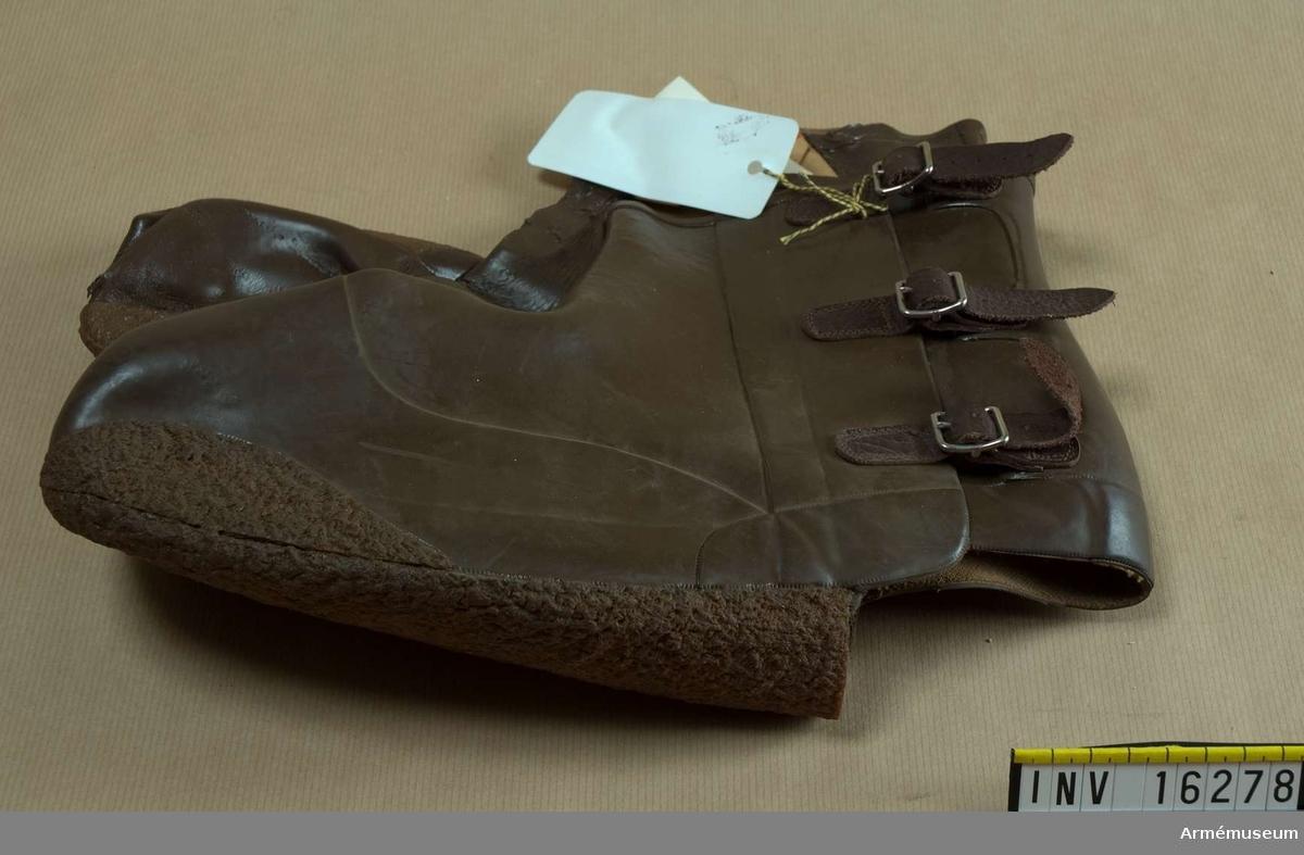Laddor arbm/1952.Av brunt gummi med förstärkning av rågummi på kanterna av  tåspetsen. Sula av rågummi. Knäppes på yttersidorna med tre spännen.1 par.