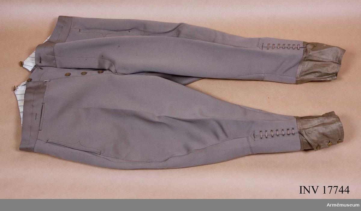 """Grupp C I. Ur uniform för officer, överstelöjtnant vid infanteriet, Frankrike. Av ljust khakifärgat diagonaltyg. En ficka på var sida och en liten ficka på framsidan för klocka. Sprund med fyra knappar, hyska och hake. Sex knappar av ben för hängsle. På baksidan en ficka med knapp och spänntamp. På tampen en tygbit med text """"G.Tydon. Avenue Bosquet -Paris. M. Rusterholz.10.10.37"""". På byxbenens nederkant en ljusgrön remsa av bomullstyg, b: 130 mm, med tre knappar och knapphål. Sju par hål för byxbenens hopsnörning.  LITT   Armée francaise. Uniformes, 1937. Album plansch 15: Officiers superieurs et subalternes (regements- och kompaniofficierare). Byxorna av ljust khakityg. Les uniformes de 1'Armée Francaise. Commendant E L Bucquoy, Paris 1935. Sida 16 """"Culote"""". Kort beskrivning på ridbyxor. Handbuch der uniformkunde. R. Knötel - Sieg Hamburg 1937. Sida 161: År 1935 infördes i Franska armén en khakifärgad uniform och officerarna fick stövelbyxor av ljust khakikläde."""
