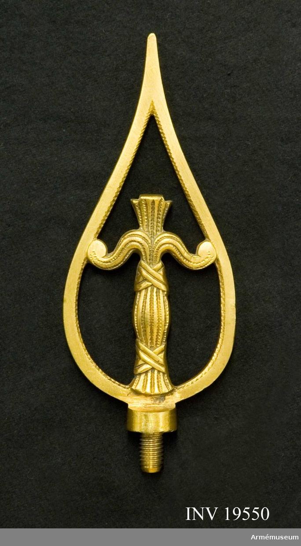 Spetsen är tillverkad av förgylld mässing. Den har en vasakärve innesluten i en spetform. Spetsen är försedd med skruv. Spetsen tillhör fana AM 19547.  Samhörande nr AM 19547-52, fana, fodral, kravatt, spets, spets, spets.