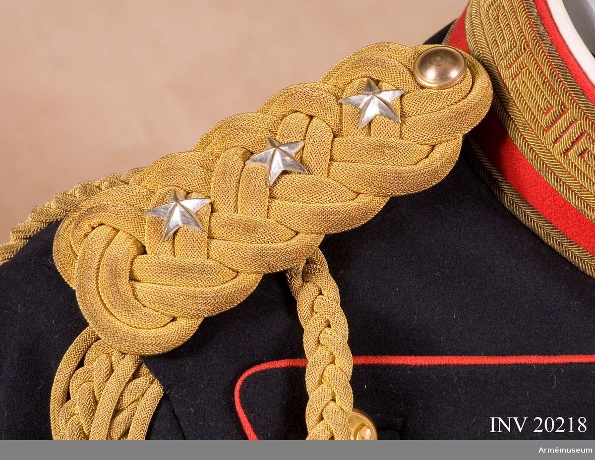 Ur paraduniform för överste vid Kejserliga Japanska Arméns generalstab. Består av syrtut med axelklaffar, långbyxor, uniformsmössa med plym, ägiljett och paradskärp. 1880, Buren 1930-talet.  Av två jämnlöpande flätade, grova, gula beläggningssnören som fästes till vapenrocken med knappar. Foder av svart kläde. Var klaff har tre femuddiga silverstjärnor, överstes grad.