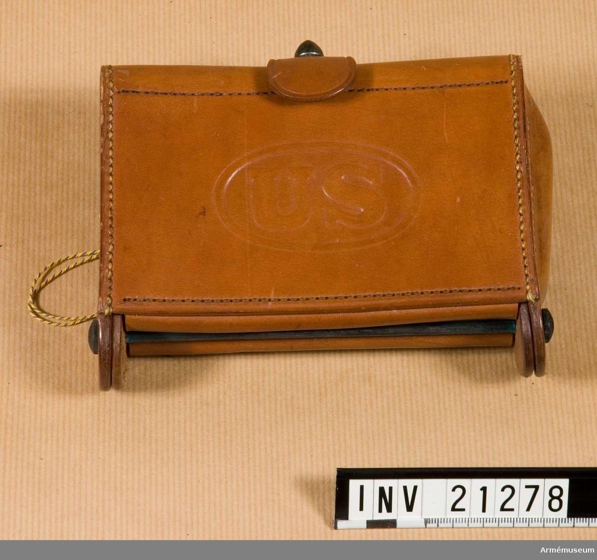"""Grupp C II. Av ofärgat läder för 20 gevärspatroner, som består av två delar. 1) En knapp av gulmetall och med stämpel på yttre sidan """"W.S"""". 2) Den andra med fastsydd läderbit med knapphål för att stänga vÄskan. På väskans baksida finns två hylsor av samma läder för att fästa den vid livrem. Inuti väskan finns fästen för 20 patroner (10 i var del) av tyg. På väskans H sida finns stämpel """"Rockisland Arsenal 1909 T.C.C."""""""