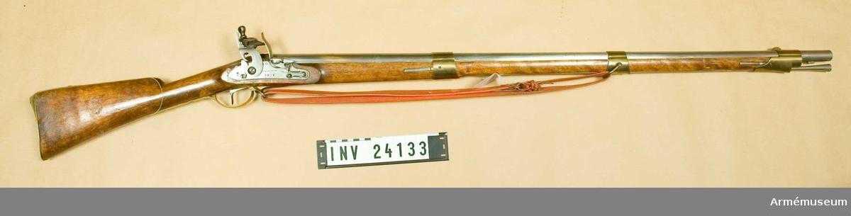 """Grupp E II b Pipa, stock, beslag och bajonett är av 1815 års modell, men flintlåset, vars bleck är märkt """"C.Helvig Invent 1808"""", har ursprungligen tillhört ett räfflat gevär m/1808. Det ursprungliga fänghålet är tärnat och ett nytt är uppborrat en bit bakom det förstnämnda.  Samhörande nr är: AM.24133-34"""