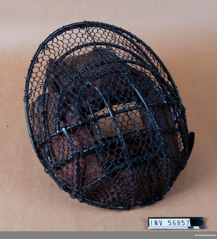 Grupp D III. Mask med ramverk av svartlackerade rundstavar av stål och däröver fäst ett nät av ståltråd, maskstorlek 10x10 mm.  Ramverket består av en oval ram, från ca kl 2-10 förstärkta med en bakre ten, ca 40 mm bakom den bakre, överänden vikt om den ovala ramen. Ifrån den bakre tenen en tvärgående båge, ifrån ovalen därovanför ytterligare två bågar. Ifrån båge två en större nedåtriktad båge nästan paralellt med ytterovalen, ifrån den nedre bågen därinnanför ytterligare två nedåt riktade bågar, ifrån den inre av dessa tvåsvagt s-formigt svängda stavar till övre delen av ovalen. Ifrån den nedre tvärbågen mellan nedåtbåge 2 och 3 och upp till bakre tenens fästen två kortare stavar. Ifrån övre tvärbågen fram en lång U-formig båge nedåt-bakåtböjd till hakskydd.  Ståltrådsnätets ändar fästade med virning om ovalen, maskor lagda om nedre tvärbågen, som troligen utgjort utgångspunkt för slagning av nätets maskor. Mitt fram vertikalt oregelbundet draget en förstärkning av en något tjockare ståltråd.  Kind-, pannskydd och hakskydd av läder med stoppade putor på insidan, siktöppning mitt fram, kindskyddet fäst med läderhälla om U-tenens bakre ände, övriga delar fria från ramen, vid hällan en läderstropp. I kindskyddet fäst två läderremmar med spänne på den ena, avsedd att fästas igenom stroppen på hakskyddet (spänne-tampen lös från skyddet). Ifrån bakre ovalringen dubbla läderremmar med ståspänne på den högra, hålremmen nyare. Ifrån öppningen i stålringen upptill en läderrem med spännhål, spänntampen saknas.