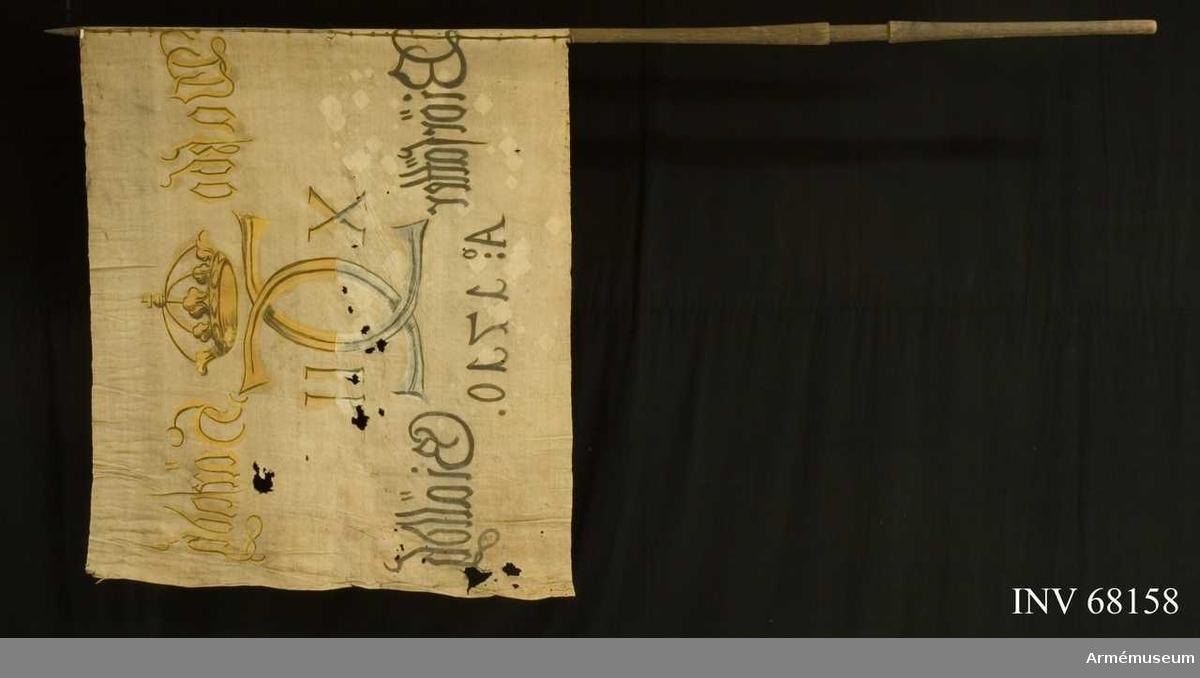 Duk: Tillverkad av enkel vit linnelärft, sydd av två horisontella våder. Fäst vid stången med en rad järnnagel på en liten läderremsa.  Dekor: Målad endast från dukens insida. Karl XII:s namnchiffer, dubbelt C med X-II på ömse sidor, krönt med sluten krona. På det övre fältet i gult och brunt, på det nedre i blått och svart. Text på ömse sidor om chiffret, upptill i gult och nedtill i svart. Under chiffret text i svart.  Stång: Tillverkad av trä. Har spets.