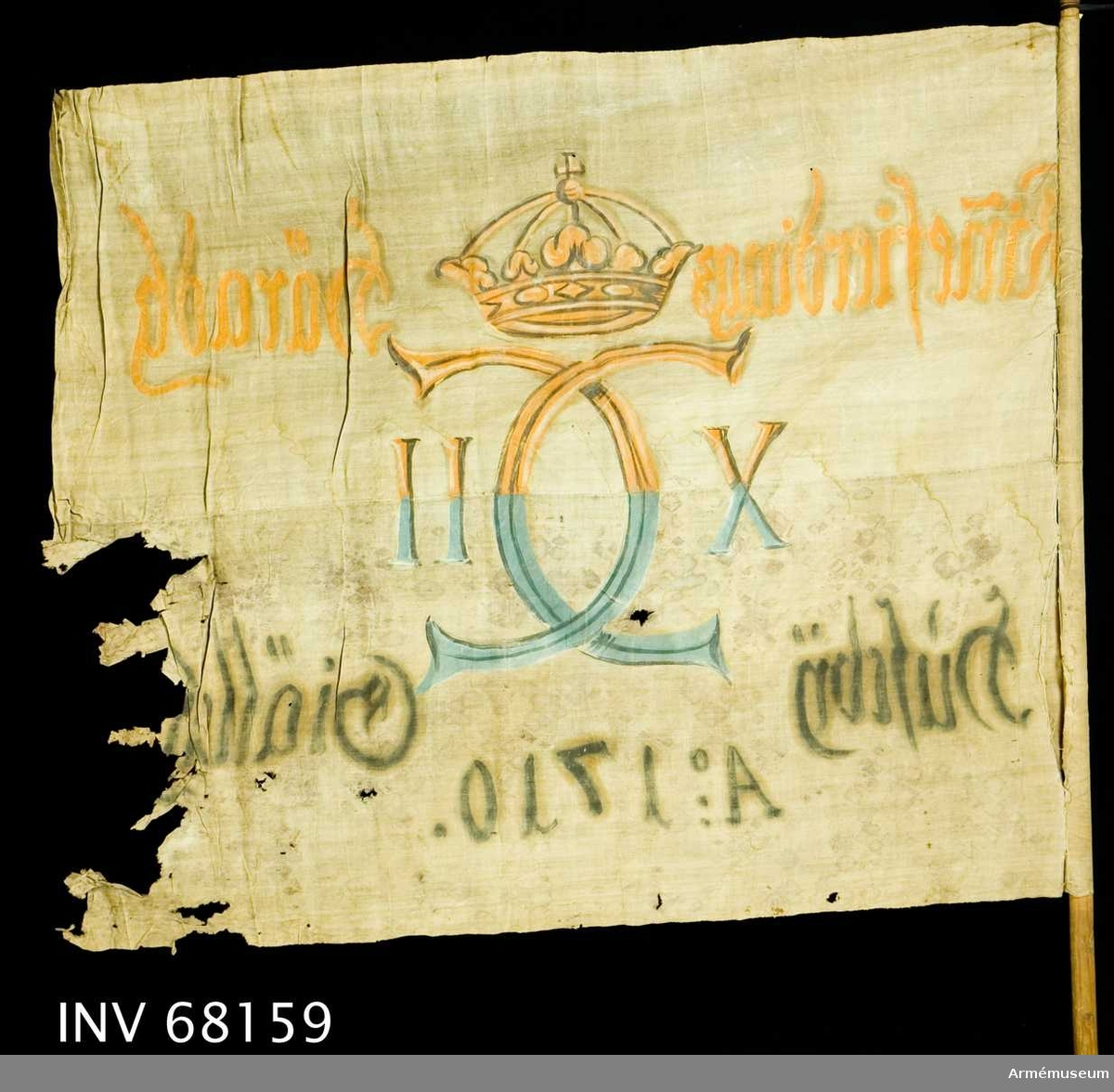 Duk: Tillverkad av enkel vit linnelärft, sydd av två horisontella våder. Duken fastsydd runt stången.  Dekor: Målad, endast på dukens insida i mitten, Karl XII:s namnchiffer, dubbelt C med på ömse sidor X-II, krönt med sluten krona. I den övre våden i gult och brunt, i den nedre våden i blått och svart. Text på ömse sidor om chiffret, upptill i gult och nedtill i svart. Under chiffret text i svart.  Stång: Tillverkad av trä. Har både holk och spets. Spetsen i form av ett hjärtformat blad.