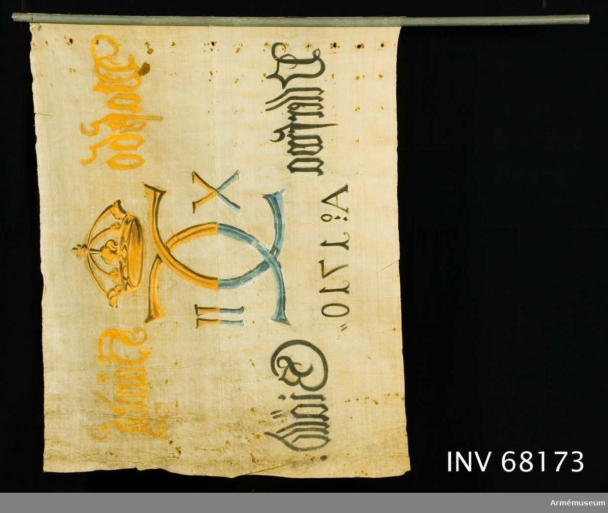 Duk: Tillverkad av enkel vit linnelärft. Sammankastad av två horisontella våder. Vertikala kantfållen lagd åt dukens utsida. Fäst med en rad järnnaglar på en liten skinnremsa, något rostfläckad.  Dekor: Målad endast på dukens utsida, i mitten Carl XII:s namnchiffer, dubbelt C, med sluten krönt krona. På ömse sidor om detta X-II i gult på övre våden, i blått och svart på den nedre.  Text på ömse sidor om chiffret, upptill i gul och nedtill i svart. Under chiffret text i svart.  Stång. Avsågad, blågråmålad.