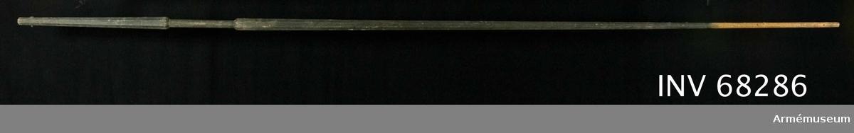 Fanstång av svartmålad furu. Åttkantig med rundat, slätt handgrepp. På övre delen spår av nithål för fästande av fanduk. Stången målad där fanduken har suttit.