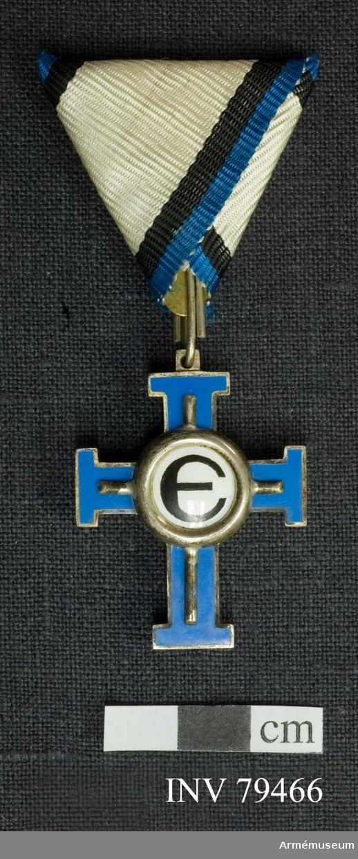 Grupp: M.  Dekorationen är till form och storlek lika med AM.016330, men färgen på korsets emalj är ljusblå.  Åtsidan: är lika med AM.016332 utom att det i upphöjningen befintliga E saknar silverkanter.  Bandets mittrand är vit, sidoränderna svarta (innerst) och blå.  Estländska frihetskorset 3:e graden 3:e klassen chevalier för civila förtjänster.