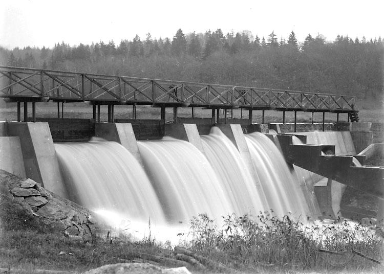 """Enligt noteringar: """"Dammen vid Trollsjön. Den byggdes som kraftverksdamm för att förse Torreby med ström. Detta blev inte av och i sjön inplanterades i stället ädelfisk. Notera även laxtrappan i dammens mitt."""" (BJ)"""