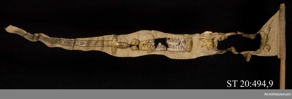 """Ursprungligen ljust röd vimpel med dekorationer i guld- och silverfärg. Inskriptionerna i kartuscherna betyder i översättning """"Må din arm styrkas"""", """"Slut din högra hand fastare"""" och """"Omgjorda dig med ditt svärd längs ditt kraftiga ben"""". På motsatt sida står """"Din hand skall sluta sig"""", """"Jesus är hans avbild"""" och """"Fienderna äro hans""""."""