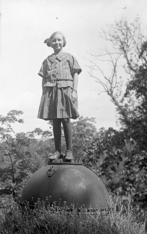 Flicka uppställd på desarmerad mina från Första världskriget