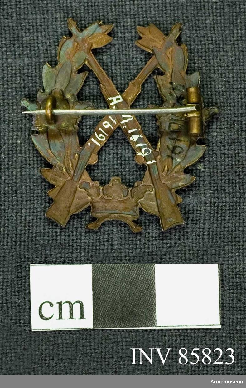 Grupp: M. Två korslagda gevär, vilande på och med pipornas översta delar inskjutna i en öppen lagerkrans. Över kransen äro trädda Sveriges tre kronor, en på vardera kransarmen och en nedtill på sammanbindningen.