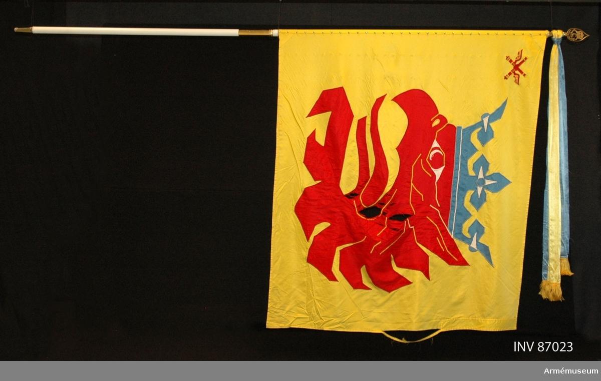 """Duk av sidenkypert med landskapet Skånes vapenbild: ett med öppen blå krona krönt avslitet rött griphuvud. I övre inre hörnet två korslagda bevingade röda eldrör av äldre modell. Detta är ett traditionsarv från Skånska luftvärnskåren, Lv4.  Motivet är huvudsakligen utfört i maskinbroderi och intarsia. Vissa detaljer är handbroderade såsom hörnmotivet, näsborren, en del av ögat samt de utskjutande delarna på ömse sidor om kronan. Duken är maskinfållad med sick-sack och raksöm. Triangelformade förstärkningar i övre och nedre stångsidan.  Vitmålad, delbar fanstång. Duken fäst med släta tennlickor. Doppsko av guldfärgad plast, troligen ej ursprunglig. Spets med Carl XVI Gustafs monogram. På holket graverat: """"Södra skånska regementet och Södra skånska brigaden 1998"""".   KT 2012-03-06"""