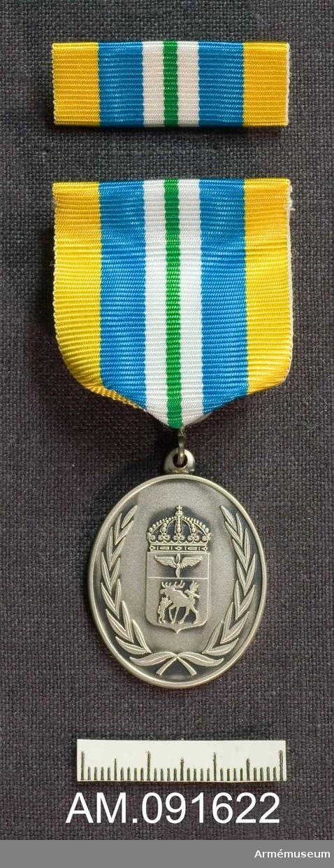 Etui innehållande medalj i silver samt släpspänne.  Märkt på framsidan med Jämtlands flygflottiljs vapen och text på frånsidan.  Band i gult med ett grönt streck på mitten åtföljd på vardera sidor av först en vit rand därefter en bredare blå rand.