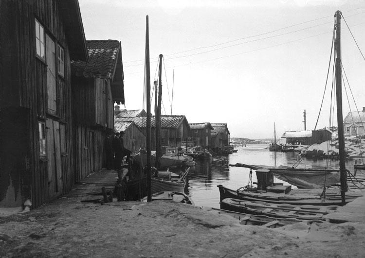 December 1923. Bryggparti, vinter med sjöbodar och båtar.