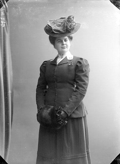 """Enligt senare noteringar: """"Ateljéfoto av en kvinna, iklädd dräkt, stor hatt och muff."""""""