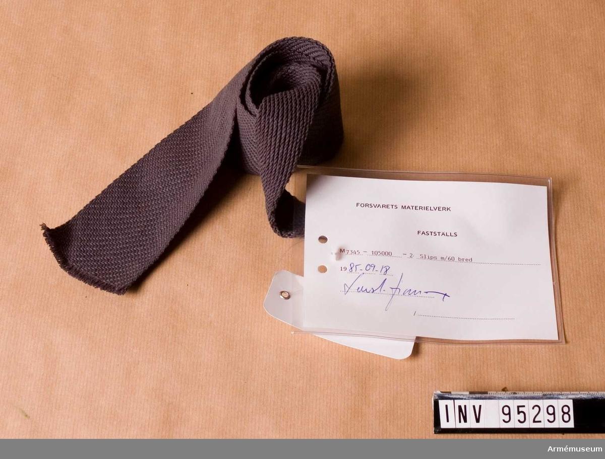 """Vidhängande etikett: """"Försvarets materielverk. Fastställs. M 7345-105000-2 Slips m/60 bred. 1985-09-18. (oläslig signatur)"""""""