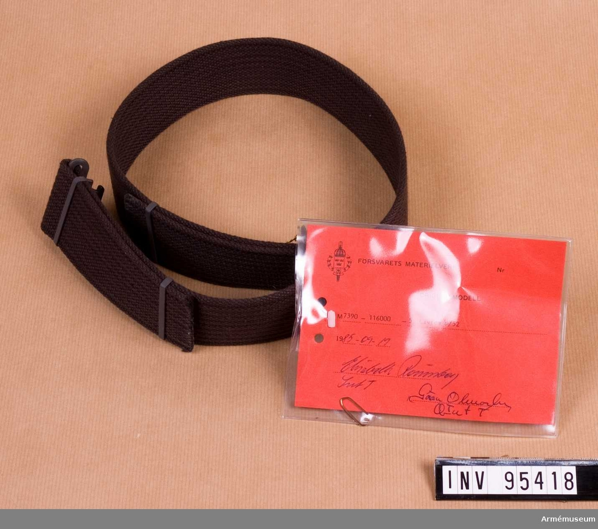 """Vidhängande etikett: """"Försvarets materielverk Originalmodell M 7390-116000-5, Livrem m/52, 1985-09-19 (oläslig underskrift)""""."""