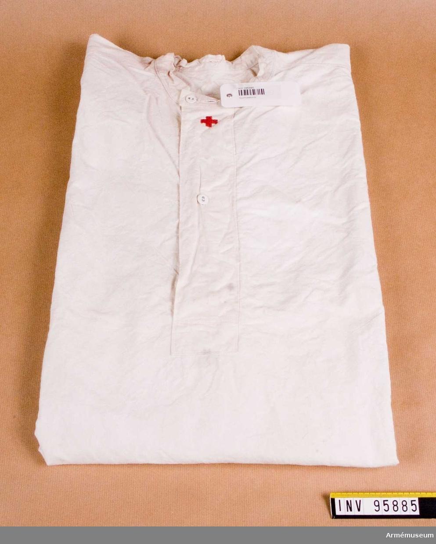 Bomullsskjorta, maskinsydd, med ett broderat rött kors.