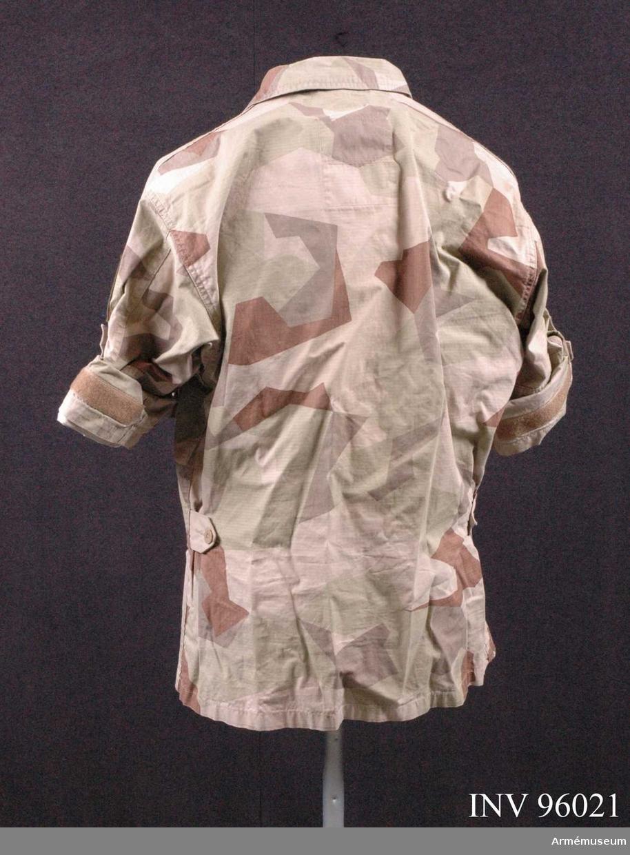 """Utförd i Ökenkamouflage. På vänster ärm: Förbandstecken (Utlandsstyrkan) och Nationalitetsmärke. På höger ärm: """"ISAF"""", """"NATO-OTAN"""". Tillverkad 2009 i Kina. Bläckfläck på vänster bröstficka."""