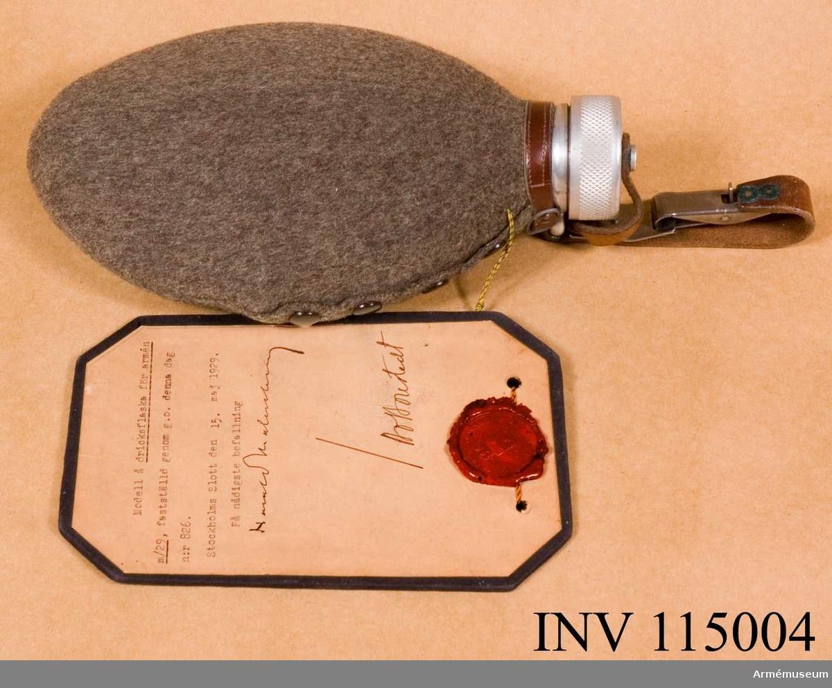 """Vidhängande modellapp: """"Modell å dricksflaska för armén m/29, fastställd genom g.o. denna dag n:r 826. Stockholms Slott den 15. maj 1929. På nådigste befallning (oläslig underskrift)."""""""