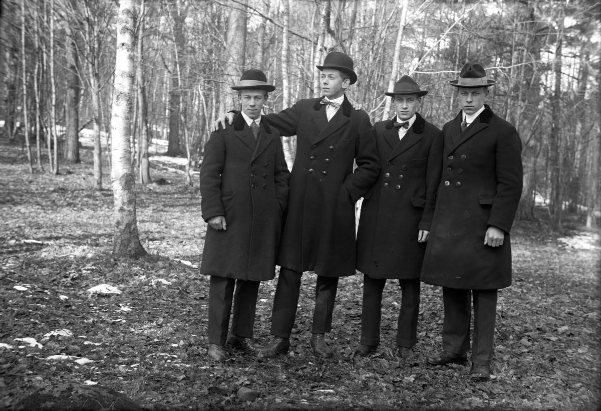 Fyra män i skogen.