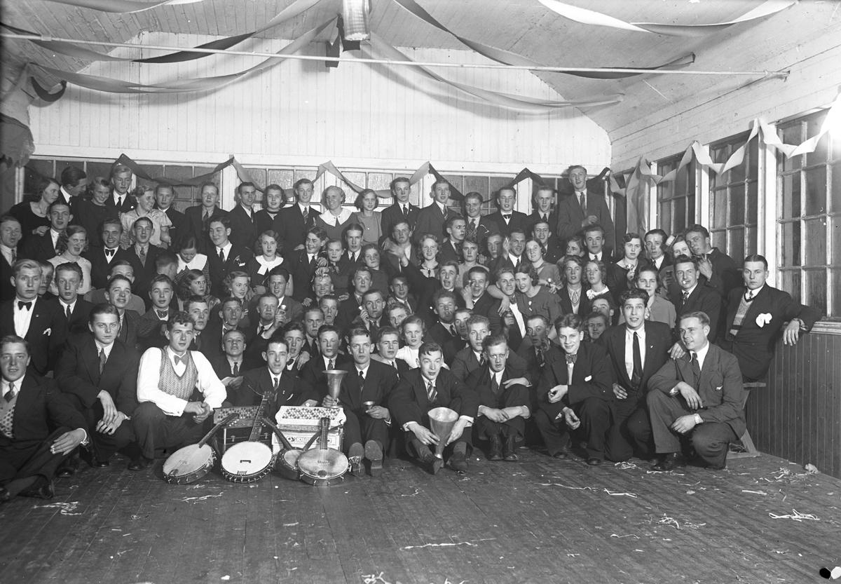Festklädda kvinnor och män i en samlingslokal. Musikinstrument ligger på golvet framför dem.