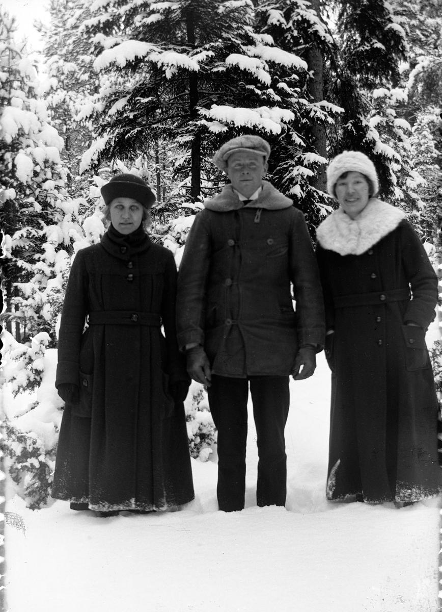 En man flankerad av två kvinnor, står i en snöig barrskog vid Lungkliniken i Eksjö.