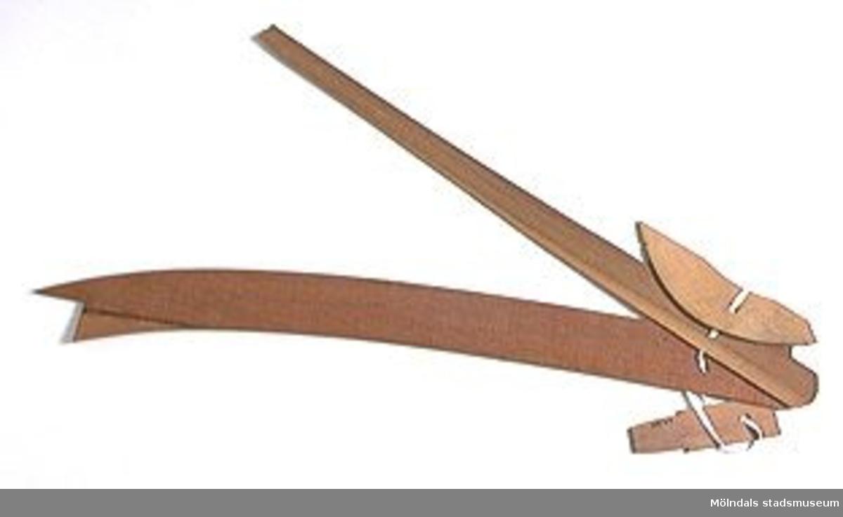 Möbelmall av trä, förmodligen detalj till soffa. En av fyra mallar (med Mölndals stadsmuseums föremålsnummer 00290-00293), ihopsatta med snöre. Litteratur: Red. Särnstedt Bo, Lindome Västsvenskt möbelsnickeri under 300 år, Stockholm 1977. Utställningskatalog från Liljevalchs Konsthall 1977-06-30 - 1977-09-11. Se sid 22-23 för historik kring fam. Thorsson.Mölndals Museum Lindomemöbler, Länstryckeriet Göteborg 1994. Utställningskatalog innehållande kapitel rörande familjen Thorssons verksamhet.