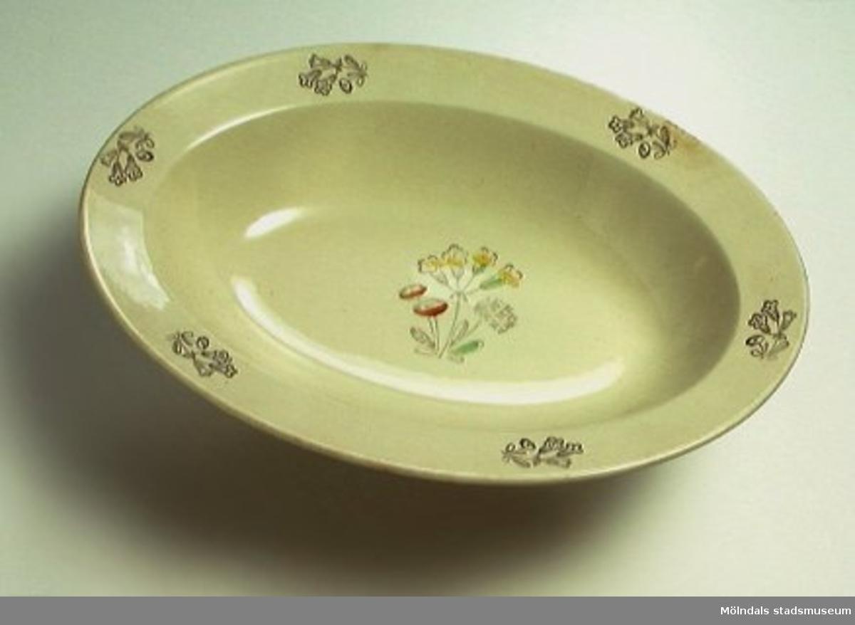 """Beigefärgad oval skål med bred kant. Blomdekor i brunt runt kanten. Blomma i brunt, gult, grönt och rött i botten. Märkt """"Rörstrand Sverige"""" i botten."""