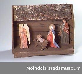 En fyrkantig stående ram avbildar ett stall. Sjutton lövsågade figurer eller andra tillbehör hör till. Figurerna föreställer Maria, Jesus, Josef, de tre vise männen, två herdar, fyra får och två änglar. Även en krubba, en palm (i lera och papper) och en stjärna (i trä på en stomme av metall och på en sockel av trä). Måtten ovan anger stallet. Taket på stallet är lite löst.