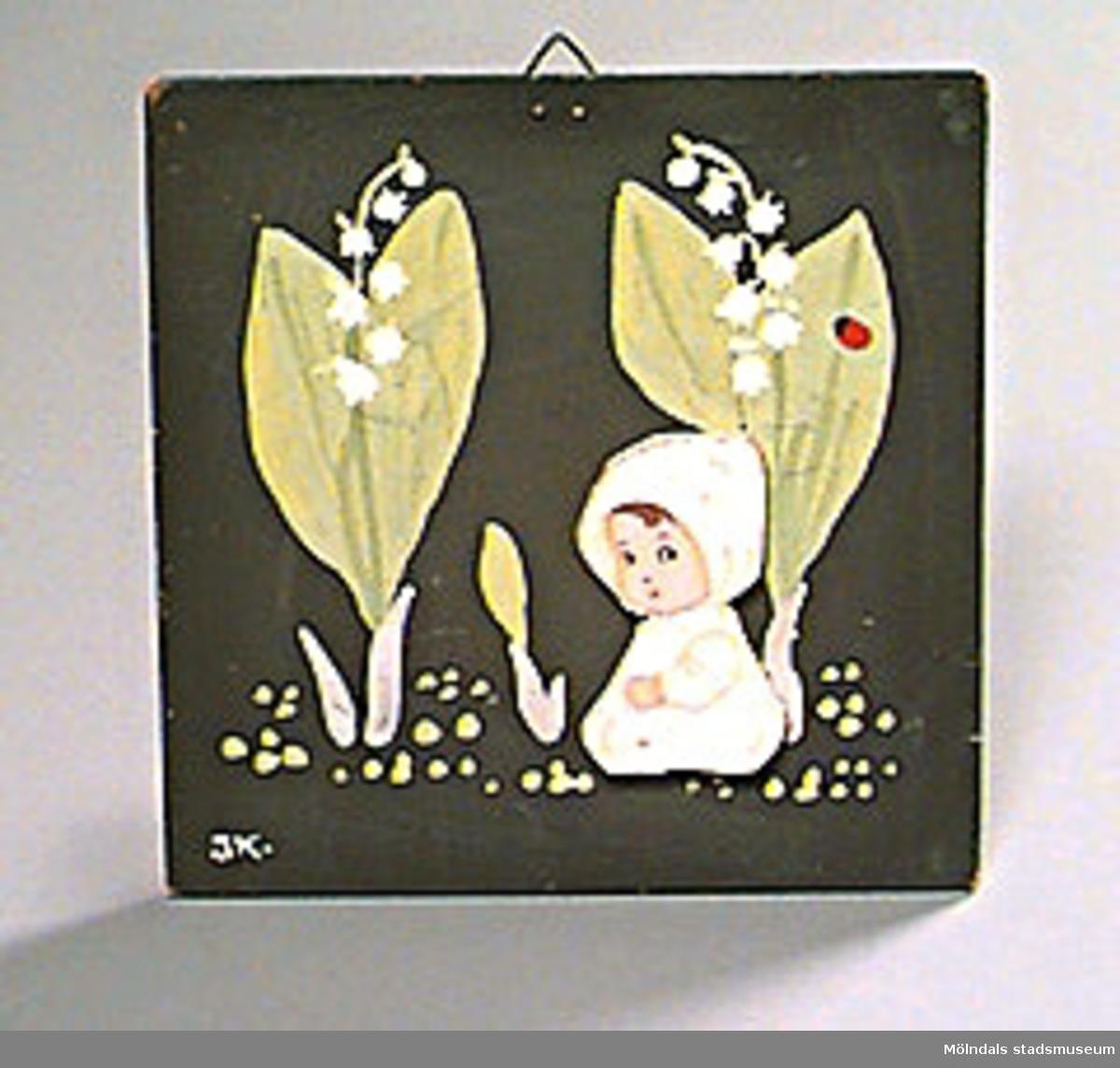 """En lövsågad figur (ett sk """"blombarn"""") i kryssfaner har limmats fast på en bit målad spånplatta. Motiv: Liljekonvaljer och ett liljekonvaljbarn.Ingegerd Kvarnström tillverkade denna och liknande träfigurer till skolor i Mölndal. Hon var en känd konstnär och själv förskollärare i Mölndal."""