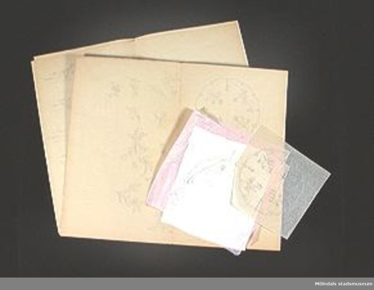 """Två dubbelvikta ark med blomskisser, ett ark med färdigt förslag målat på grått papper, avritat mönster, påbörjat broderi. """"VITBRODERI, FÖRSLAG TILL DUK"""".Elevarbete från textillärarseminariet.Gåvan förmedlad genom Gustav Wickström."""