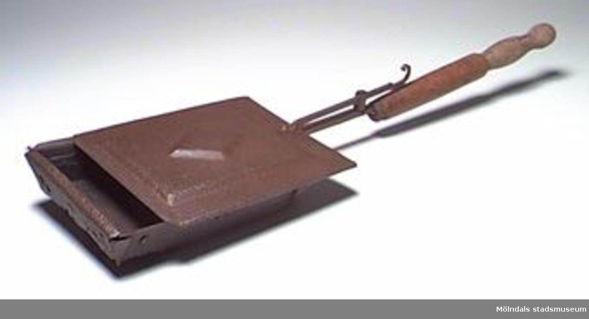 Kafferostare/kaffebrännare för att rosta (bränna) kaffebönor i. Rostaren har skaft och skjutlock. Lådan är ursprungligen lagad flera gånger genom pånitade plåtbitar, men den är ändå genomrostad (rostskyddsoljad). Ett containerfynd.Tidigare sakord: kaffebrännare.