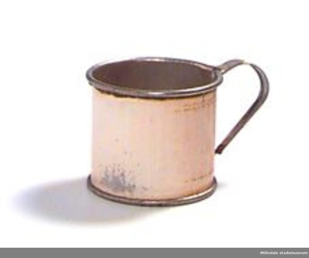 """Kaffemått av rostfri plåt i form av en bägare med ett öra lött på. Rymmer ca 2/3 dl. Utsidan belagd med en gulaktig färg och guldfärgade dekorlinjer som är delvis bortnötta. Texten """"ELMA KAFFE"""" knappt läsbar.Rester av malet kaffe.Ägaren är faster till givaren."""