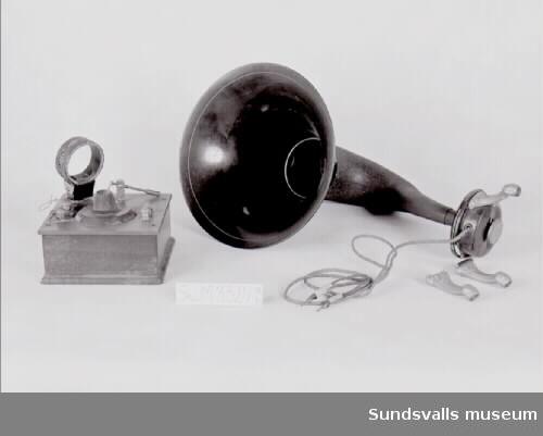 SuM 3329:a-b kristallmottagare med tillhörande högtalartratt. SuM 3329:a kristallmottagaren består av en brun trälåda med flera olika komponenter upptill, bl.a. en metallspets som är placerad mot en kristall av blyglans.  SuM 3329:b högtalartratten är tillverkad i svart metall, står på tre ben och har trådöverdragna sladdar. Tratten är av märket 'Salon'.