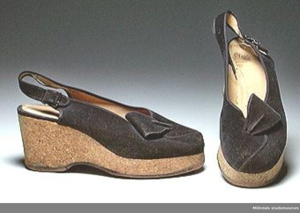 """Ett par höga, svarta skor i mockaimitation. Sula och klack i ett stycke av massiv kork, s k kilklack. Sulan är närmare 30 mm hög, klacken 70 mm hög. Skon knäpps med slejf runt den bara hälen. Sulan (ev. hela skon) tillverkad av Tretorn AB, Helsingborg, """"Durolit"""". Märkt """"Made in Sweden"""". Tåjärnsförsedda.Lite nötta på insidan och slitna under klacken.Tidigare sakord: damsko, par."""