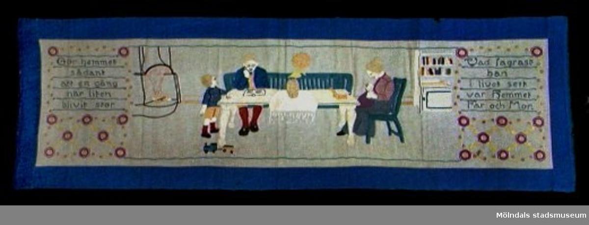 """Broderad väggbonad med 60 mm bred blå bård. Brodyrduken är av linne. Motivet: Familjebild. Far läser högt ur bok, mor syr och barnet leker med tåg. Text: """"Gör hemmet sådant att en gång när liten blivit stor, Vad fagrast han i livet sett var hemmet, far och mor""""."""