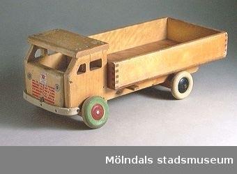 Lastbil med tipp helt i trä, ett hjul ersatt med massivt trähjul.Ingår i Holtermanska samlingen.
