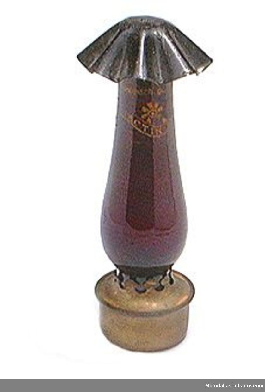 Spritlampa i rött glas, användes som mörkrumsbelysning vid framkallning runt 1900-talet.3 delar spritbehållare, lampglas och hatt.