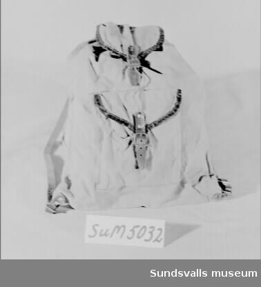 Ryggsäck i ljusbrun bomullscanvas med bärremmar i läder och metallspännen. Ryggsäcken stängs med dragsko och ett lock med rem och spänne. En ficka med lock som stängs med läderrem och spänne. Ryggsäcken har använts av givaren, född 1930, som skolväska.