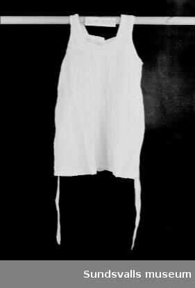 Flickförkläde i vitt bomullstyg med axelband, knäppning bak med två knappar, samt knytband i midjan. Brodyrfält på förklädets övre hälft.