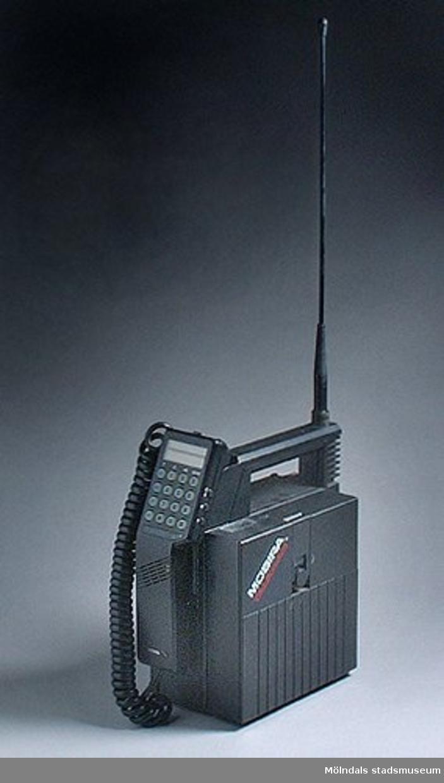"""Mobiltelefon 03678:1 samt bruksanvisning 03678:2. Telefonen tillverkades 1987 och kostade 20 000 kr då den köptes 1988. Den användes under ca tio år. Ägaren arbetade som konsult och behövde telefonen i arbetet men fick betala en stor del själv. Telefonen monterades in i bilen, och när man bytte bil vartannat år, flyttades mobilen till den nya bilen. Under semestrar monterade de ibland loss den från bilen och flyttade över till husvagnen.Familjen skulle åka till bekanta en helg, och väl framme kom de på att de glömt badkläderna. Nils skulle åka hem och hämta dem. Lotta ringer till Nils och första frågan till honom är """"Var är du nånstans?"""" - Stort skratt bland vännerna. """"Det vet du väl var han är!"""". Så ovanlig var mobilen då."""