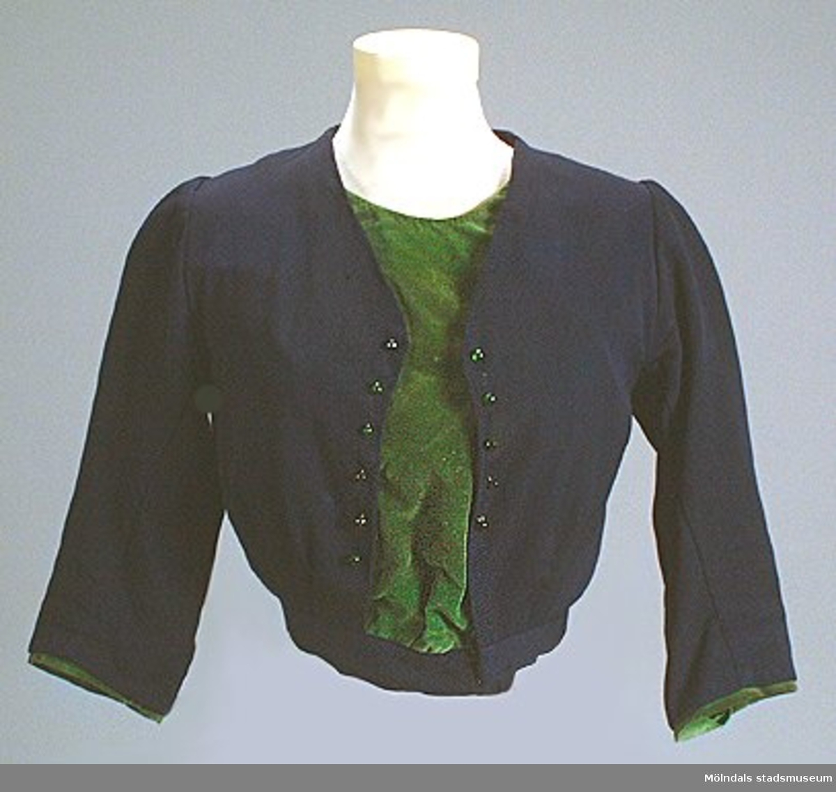 Kraglöst klänningsliv i mörkblå ull med grön sammetsbesparing. Livet är garnerat med små gröna glaspärlor. Fodrat och omsytt.