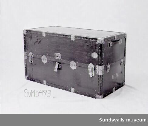 Svart koffert med metallbeslag och lås. Sidohandtag i läder.