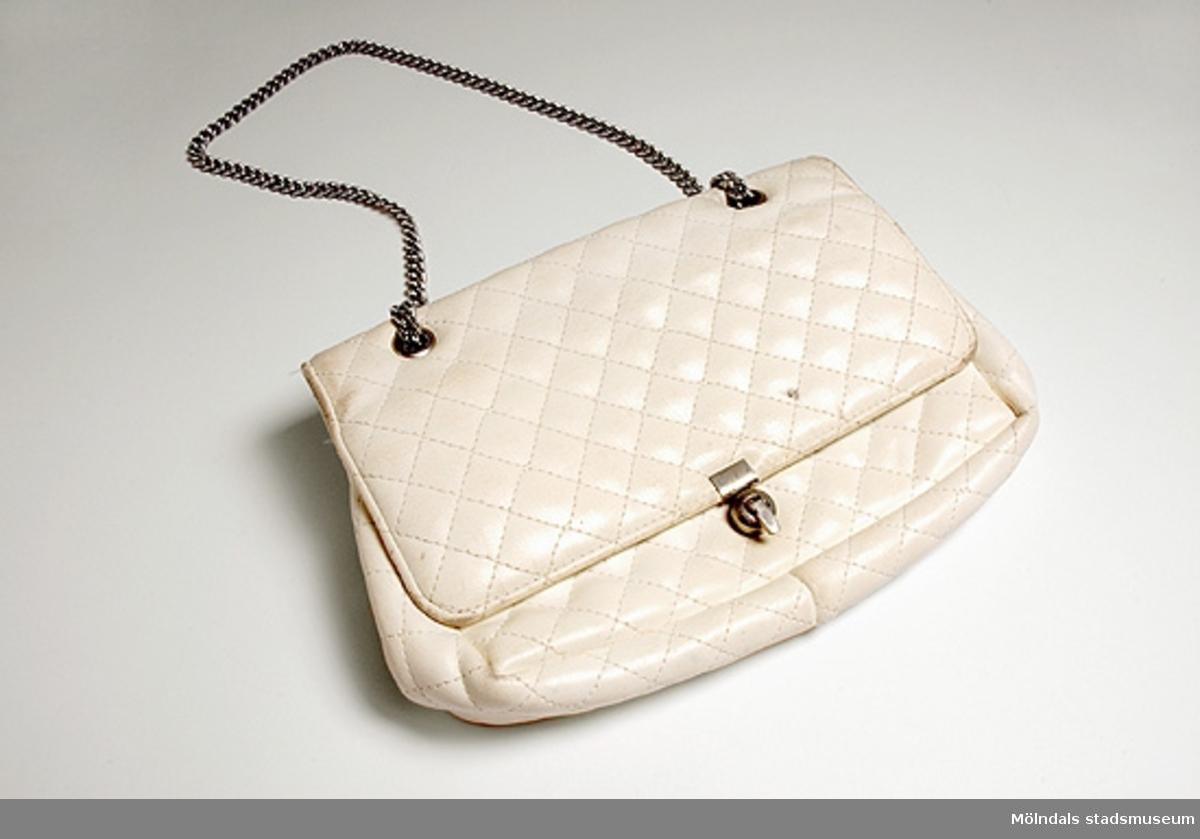 En vit damhandväska av Chanel-typ i konstläder, med en lång vitmetallskedja, som löper i öglor genom locket. Hängs över axeln eller bärs i handen. Inredd med olika fack. Tillverkad i Kållered hos Brandahls väskfabrik.Givaren/användaren köpte väskan 1963, för att ha vid en skolavslutning. Givaren hade sytt en klänning med jacka till och denna väska matchade det sydda.
